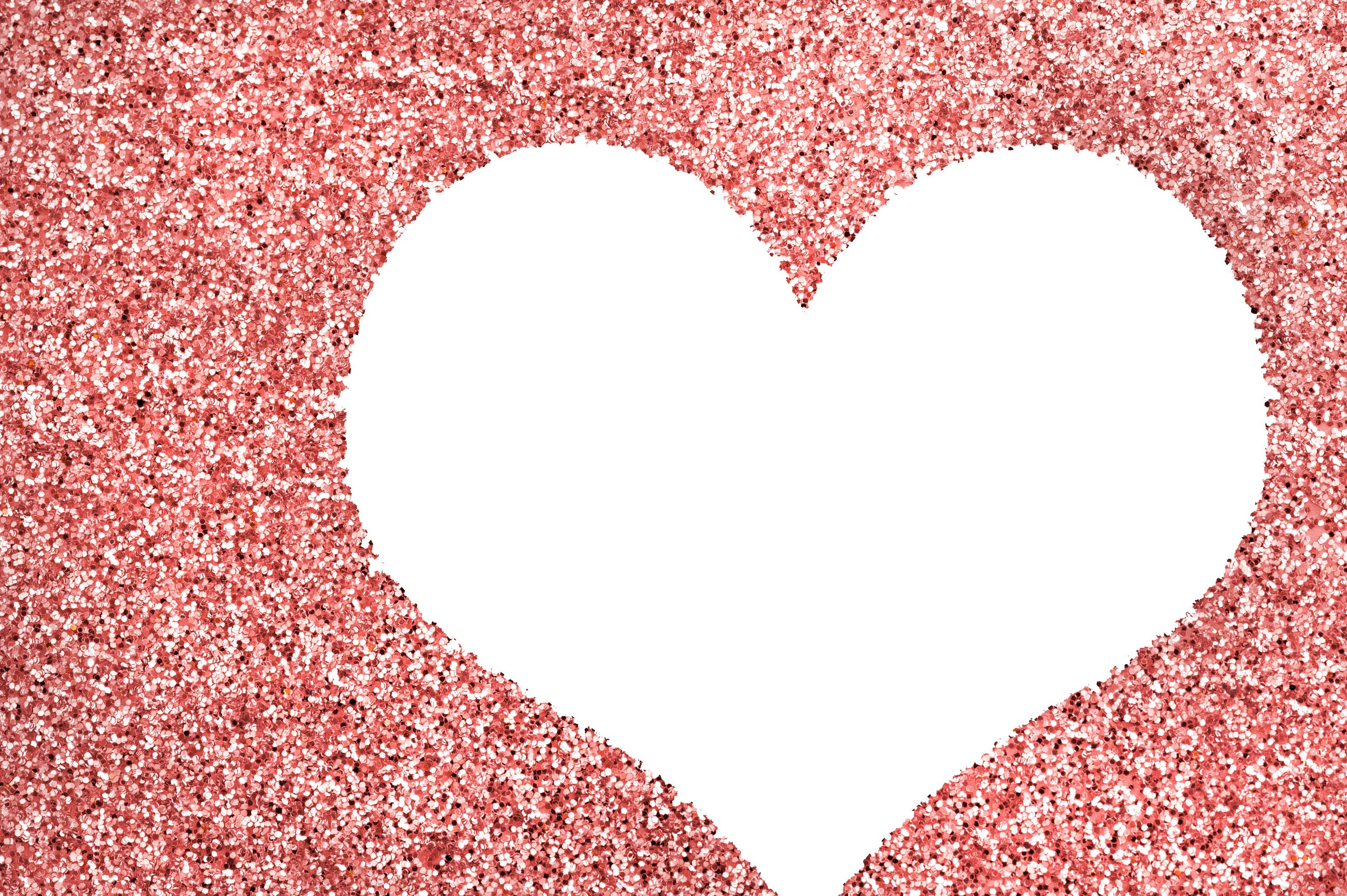 Blank white heart with copyspace for your greeting to a sweetheart or loved one in a textured red glitter background symbolic of love and romance for Valentines Day